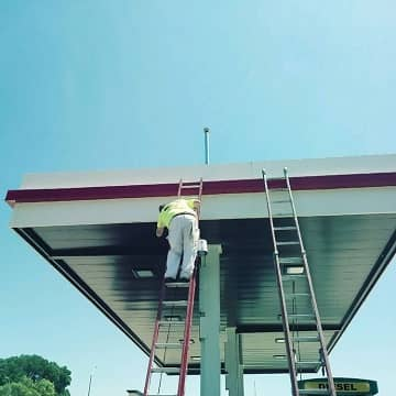 man on a aldder painting a gas station