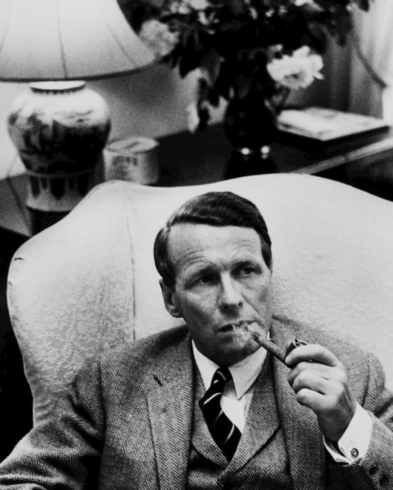 David Ogilvy sitting in an armchair, smoking a pipe.