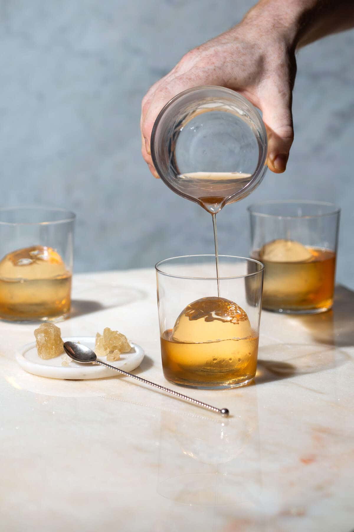 whiskey being pored onto large ball of ice