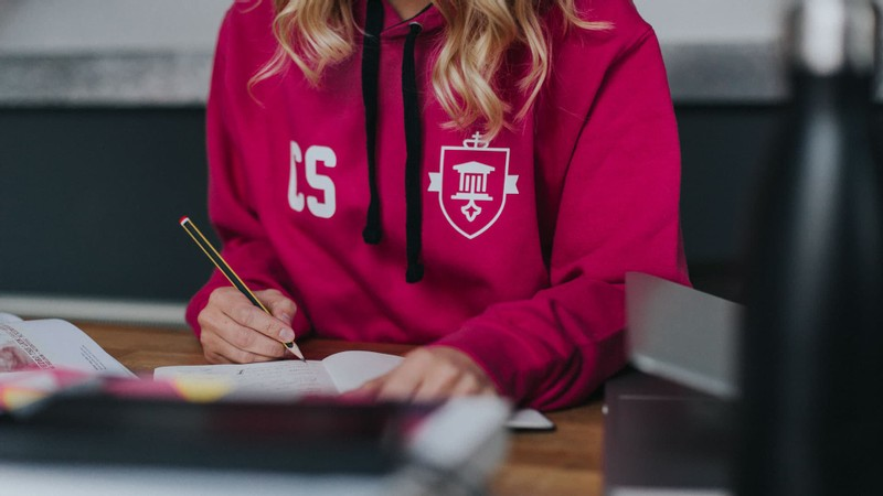 A blonde girl in a hot pink leavers hoodie with the school crest printed on the chest