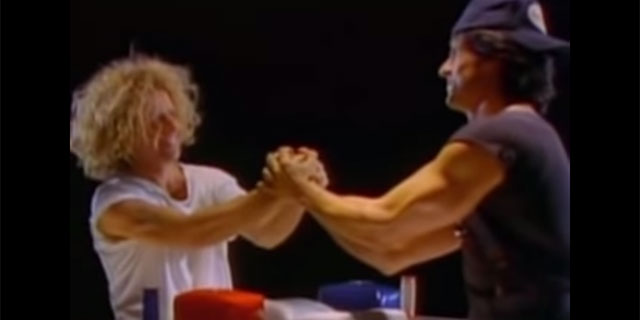 Sammy Hagar and Sylvester Stallone arm wrestling in the Winner Takes It All video from the Over the Top soundtrack