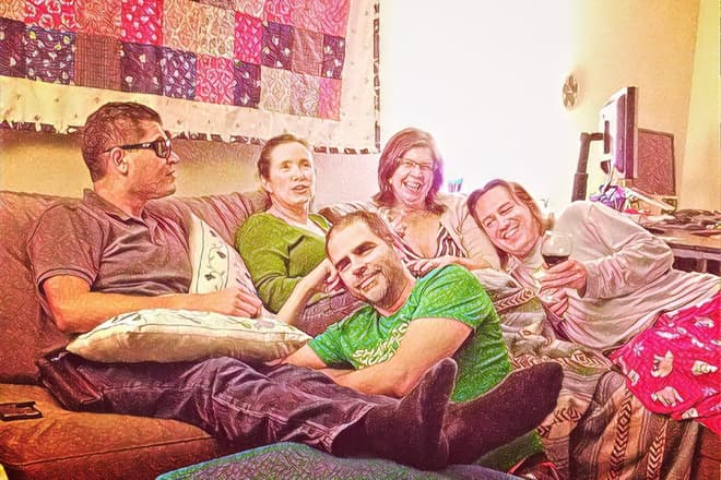 Five friends on a couch, enjoying a bottle of wine.