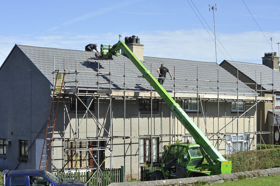 roofers using roofing calculators to work on a house covered in shingles and scaffolding