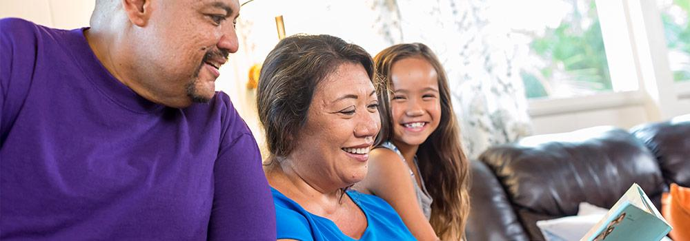 Hawaiian grandparents are shown at home visiting with their granddaughter