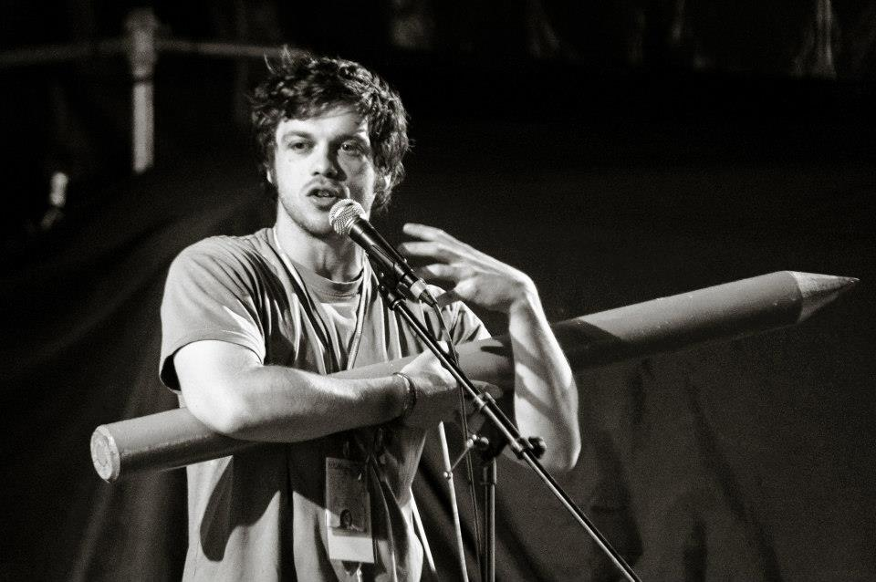 A black and white photo of Adam Kammerling, a scruffy 20-something, holding a giant pencil and talking into a mic