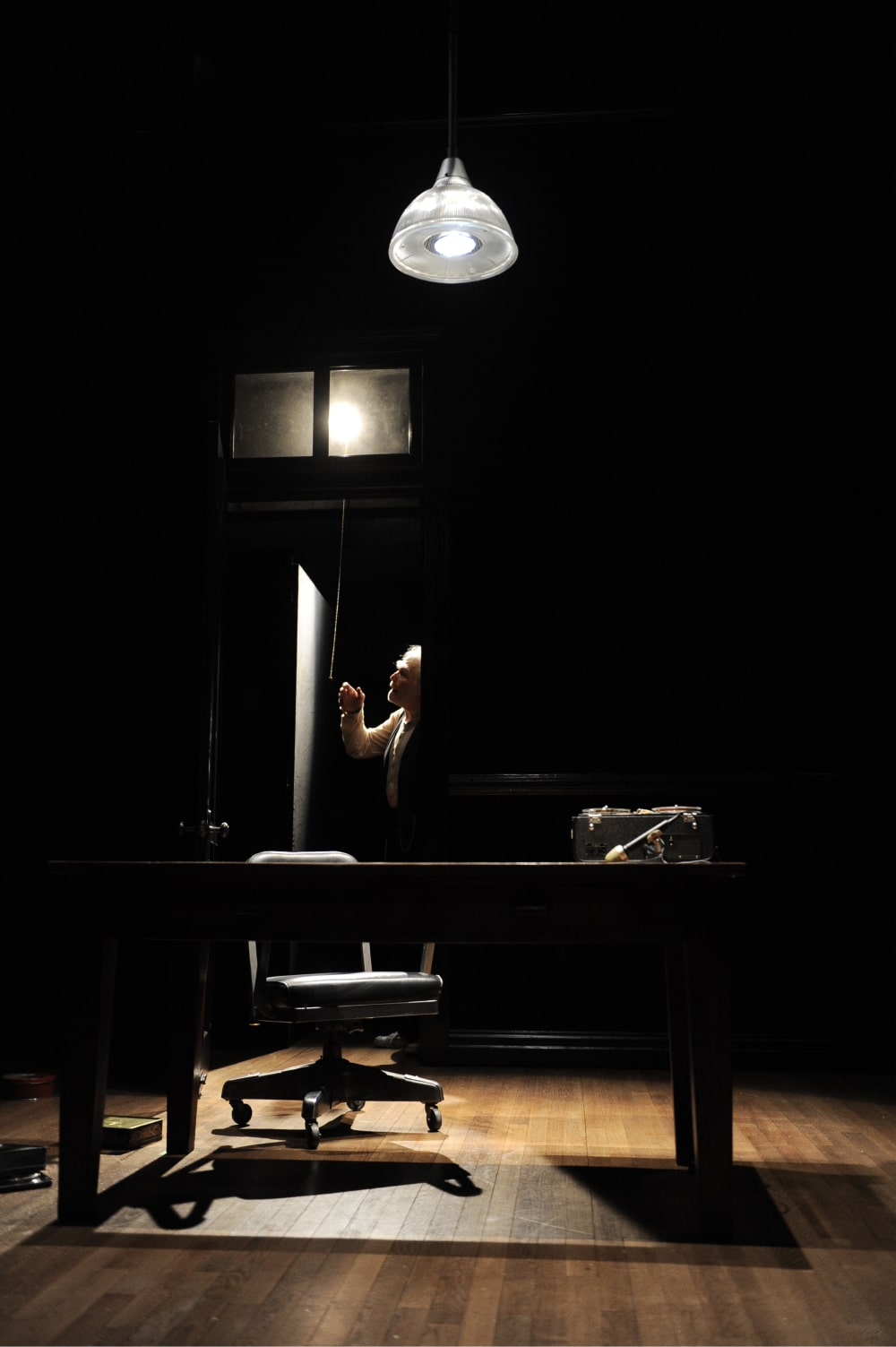 Starkly lit man in closet reaches for light pull-chain, foregrounded by desk under hanging lamp.