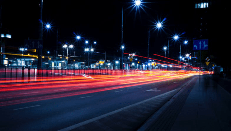A dark night with streetlights on and a red flash of light from a car photographed with a slow shutter speed.