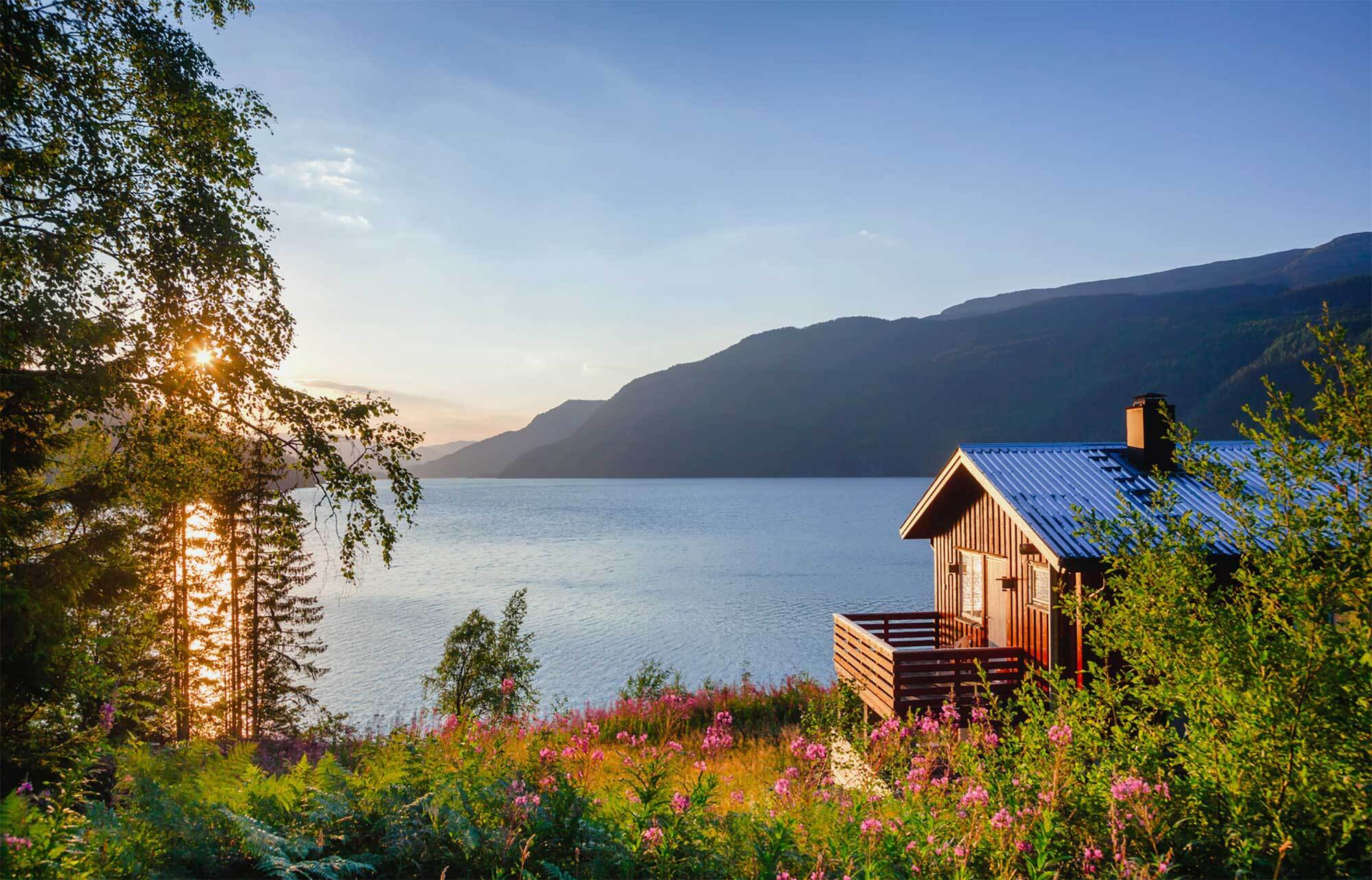 Cabin in front of lake and mountains.