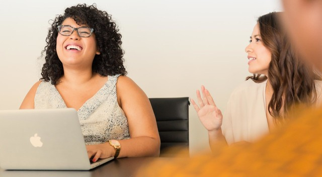 Two women laugh together at an office