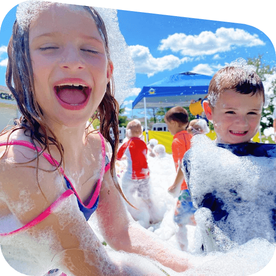 Smiling kids playing inside foam.