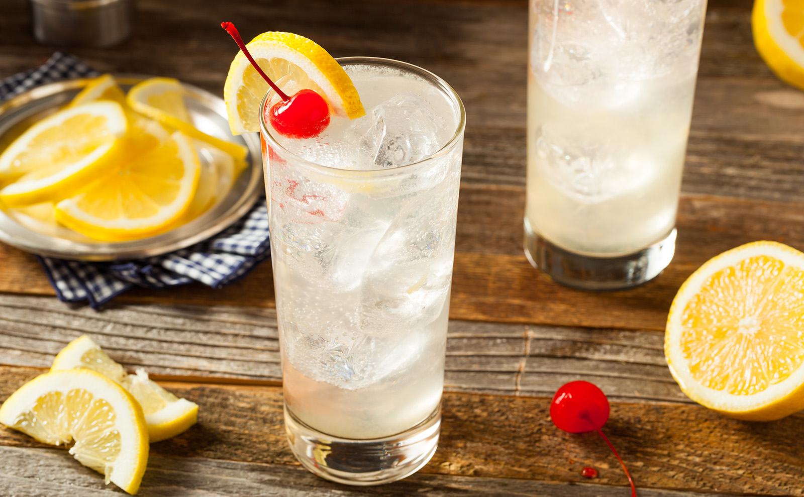 tom collins cocktail sitting on a wooden bar