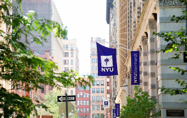 NYU Steinhardt campus flags hang over a sidewalk between campus buildings