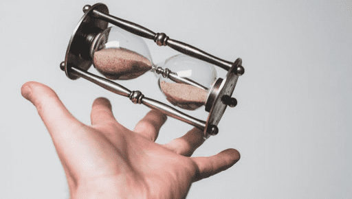 A person's hand spinning a sand-filled egg timer in front of a grey background.