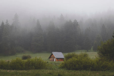 An off-grid rang in Oregon with solar panels on the roof, with foggy trees in the background. Photo from Alex Bierwagen of Unspalsh.
