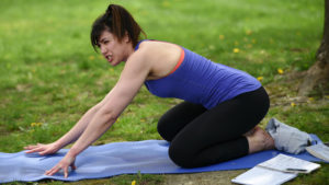 Woman doing yoga on a yoga mat in a park