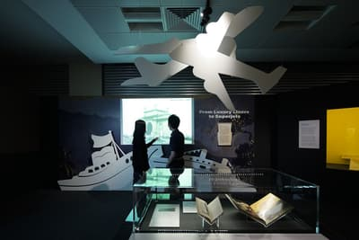 A photo of the From Luxury Liners to Superjets section, with a man and woman looking at a projected image in the background. Cut-outs of paper plans are hanging from the ceiling. In the foreground, there is a showcase featuring images and books.