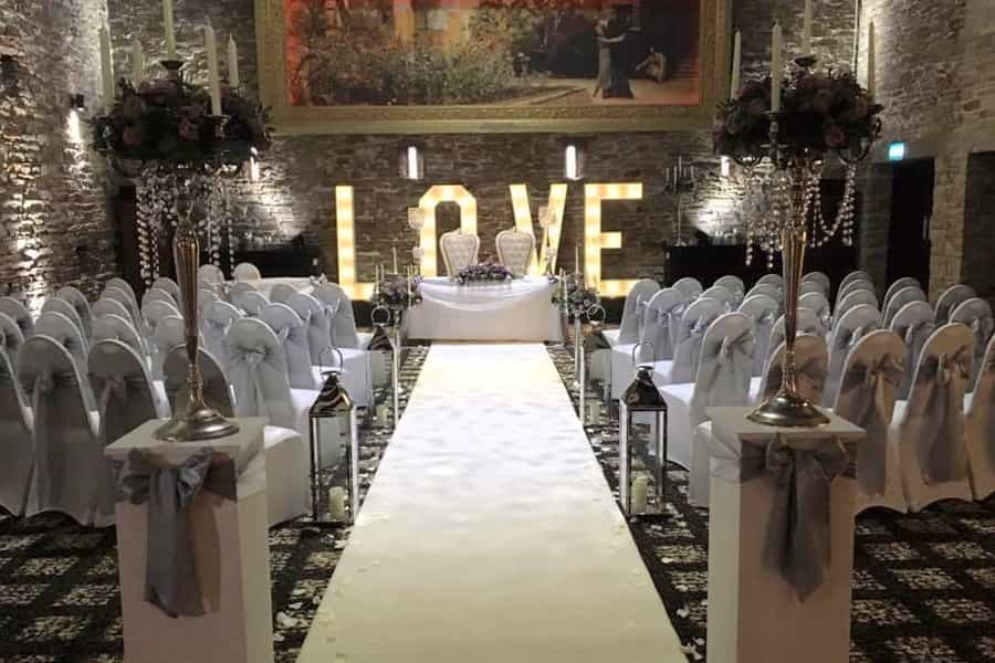 illuminated love letters at the end of a line of wedding ceremony chairs