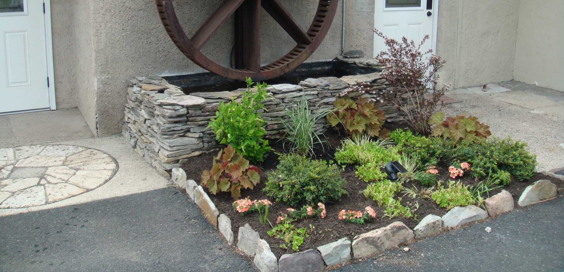flower bed in front of old wheel