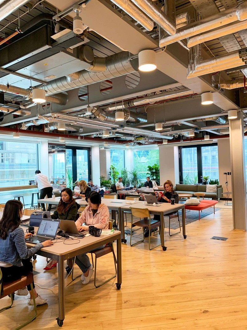 Employees in an open workspace layout with exposed ceilings