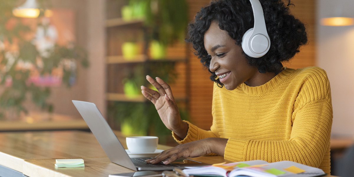 A woman sitting at a table smiling at a laptop, wearing headphones