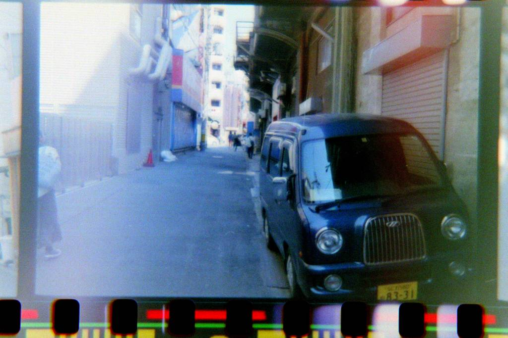 Photographic Negative of a car in an alleyway, now it looks like a regular photo