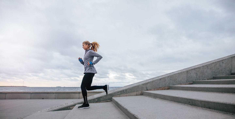 Eine Frau joggt eine Treppe hinunter - Niedrigzinsen - Was bedeutet es für mich und wie kann ich meinen Vorteil daraus ziehen