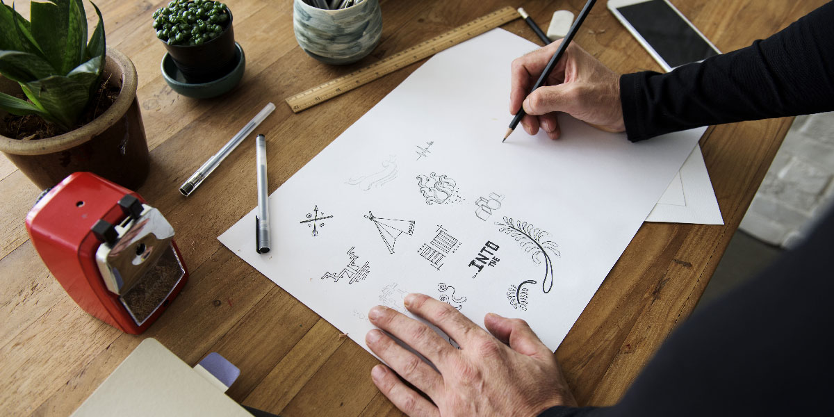A UI designer's hands sketching some user interface icons