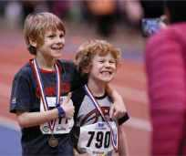 Kids smiling for a photo wearing track and field medals