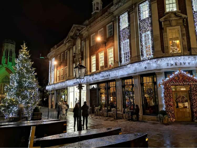 A photo of St Helen's Square, York at nighttime. A christmas tree is to the left of the picture, lit up in gold and white lights, with the restaurant, The Ivy, to the right, also covered in white lights.