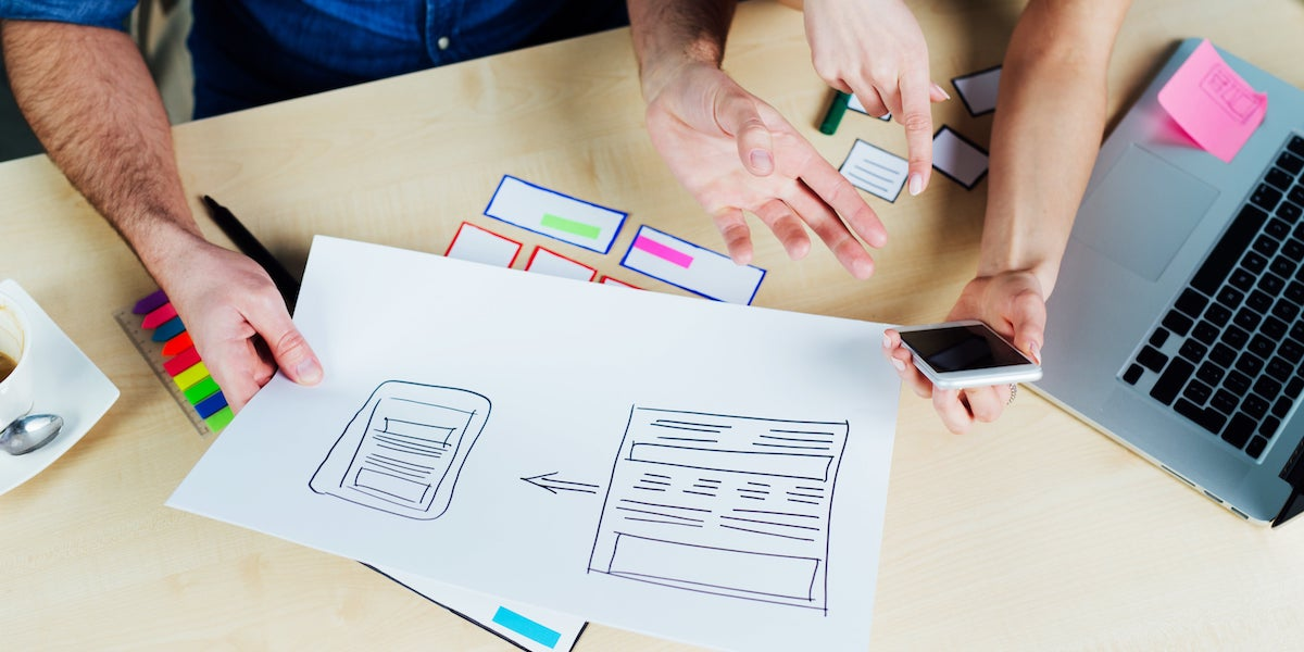 Two UI designers work on different mock-ups for an app UI