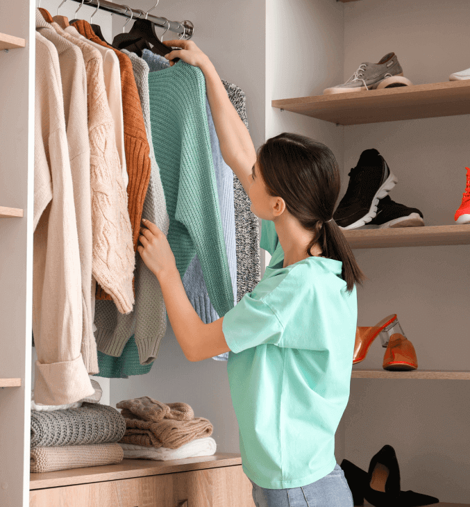 Woman who removes a piece of clothing from her wardrobe.