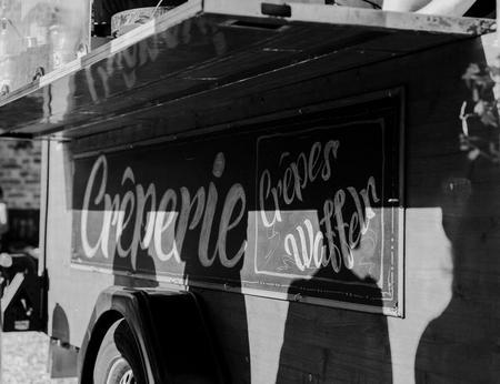 Schwarz-Weiß Aufnahme eines im Retrostil beschriebenen Crêperieschildes an einem Food Truck