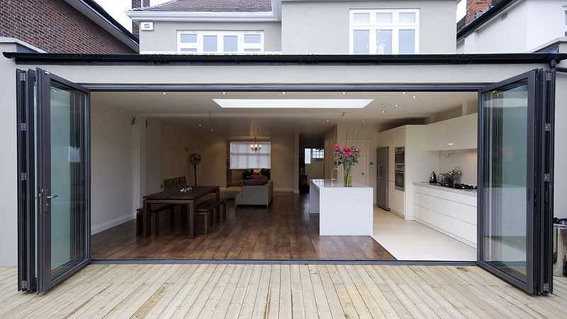 Rear facing kitchen dinner extension with bi-folding doors leading onto garden decking