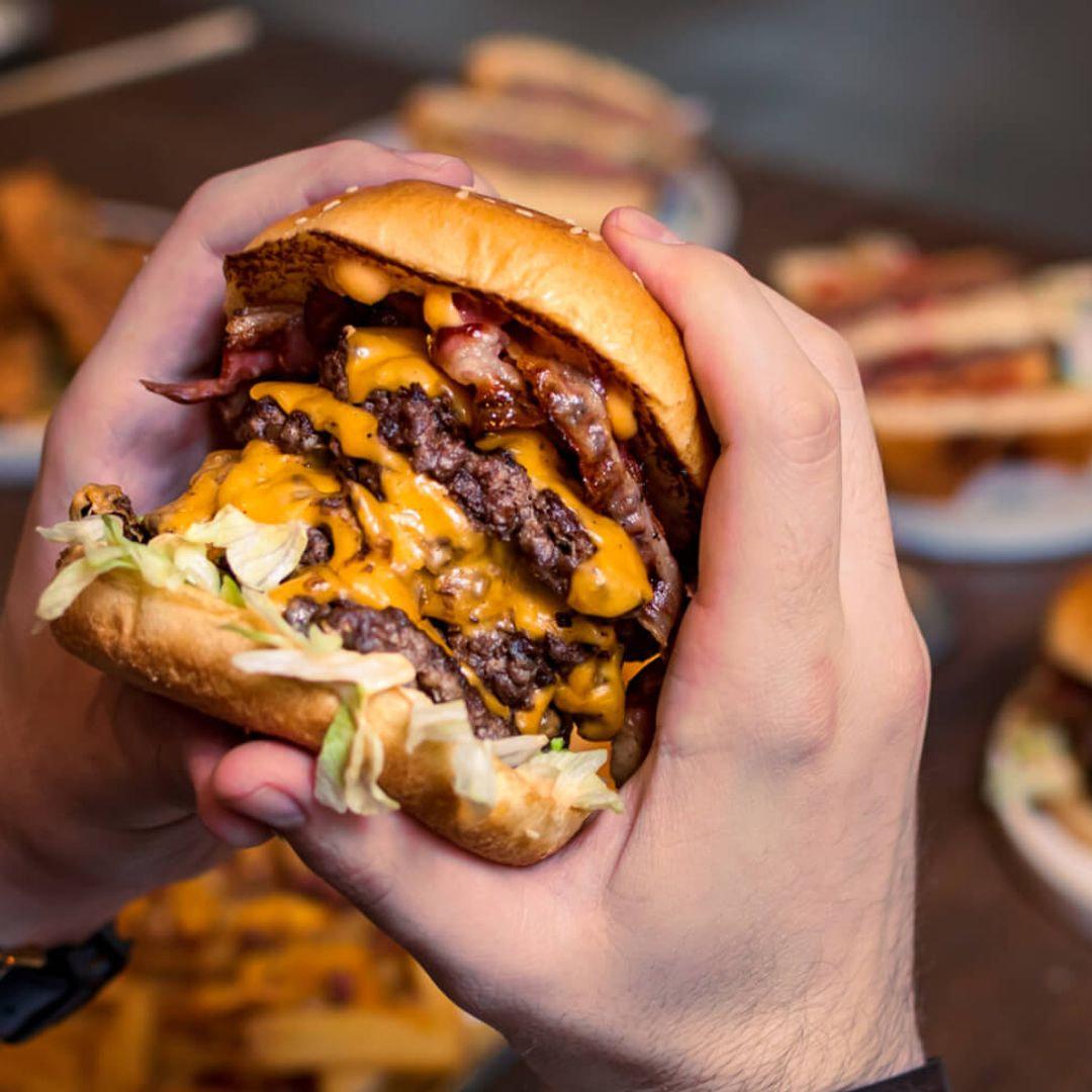 Slap & Pickle - burger in hands Beer Hawk - credit Thom Archer