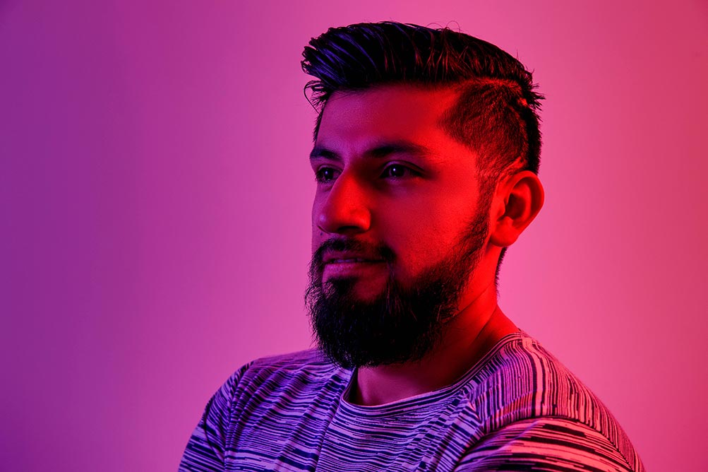 A bearded man stares into the middle distance under a vivid, neon light.