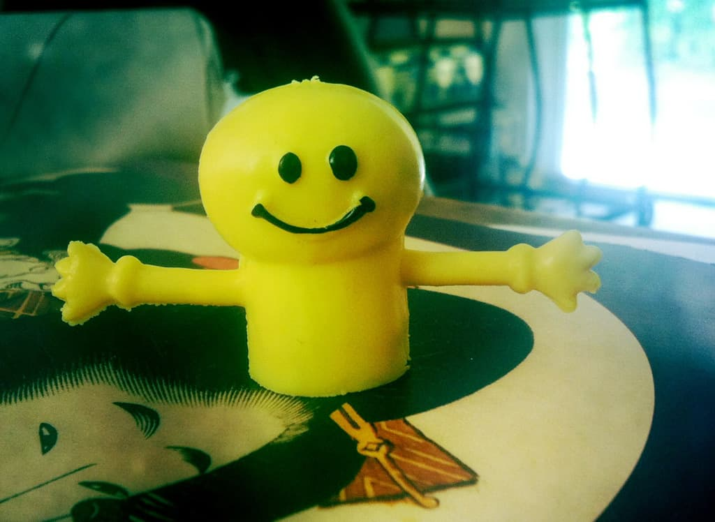 A yellow smiley-face finger puppet