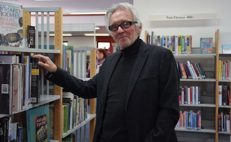 A man in jacket and glasses by a bookshelf.