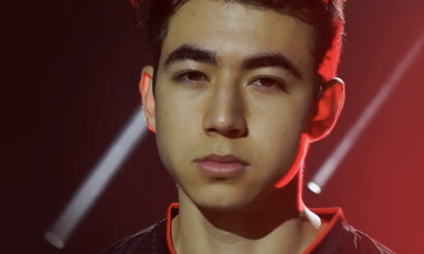 Faze Attach posing seriously in esports jersey on dark red stage with spotlights in background