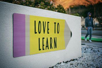 Love to learn written on a milestone rock