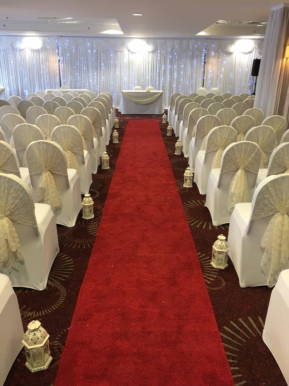 Wedding ceremony with red runner and sparkling backdrop