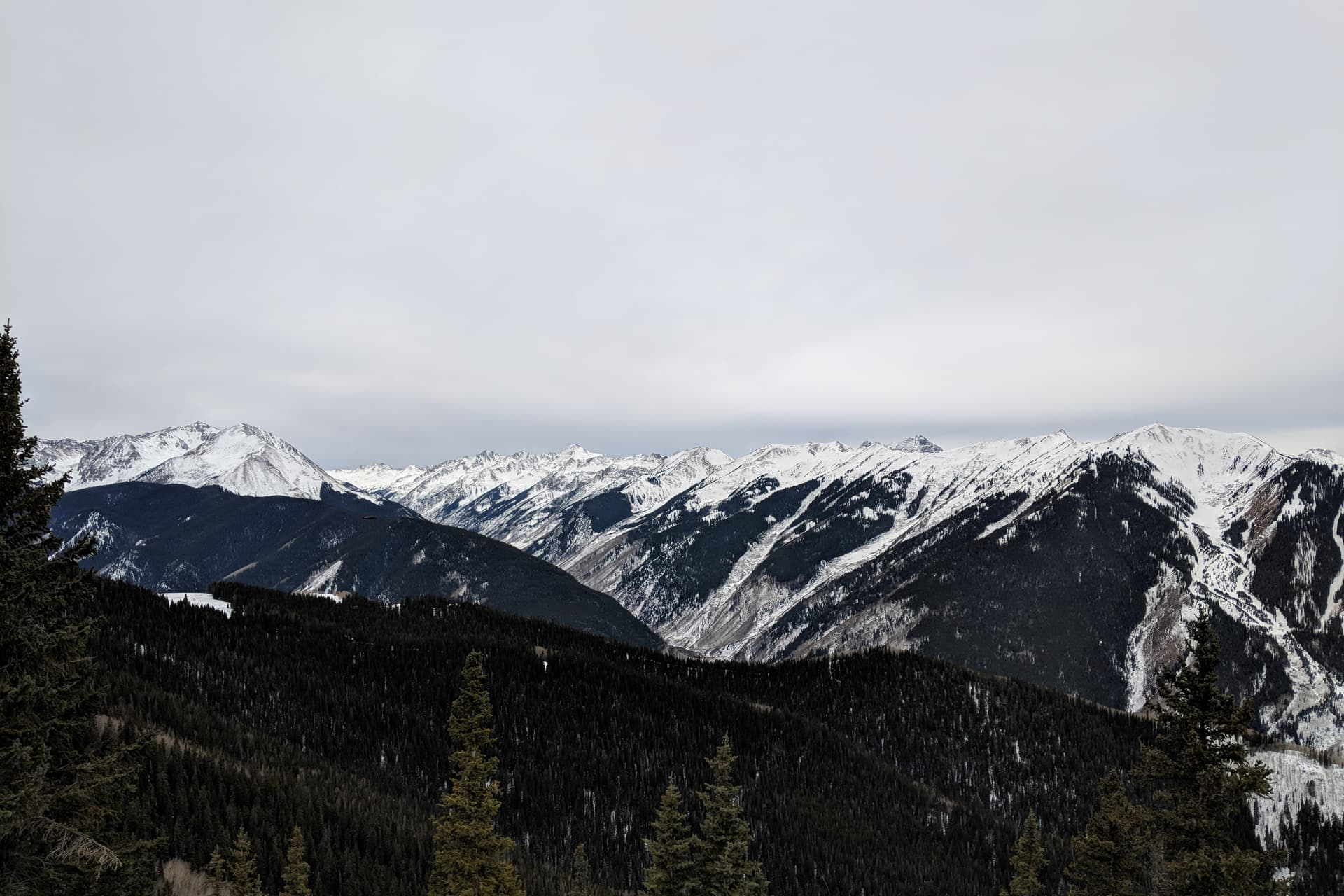 Snow-capped mountains border a steep valley. The winter sky is cold and gray.
