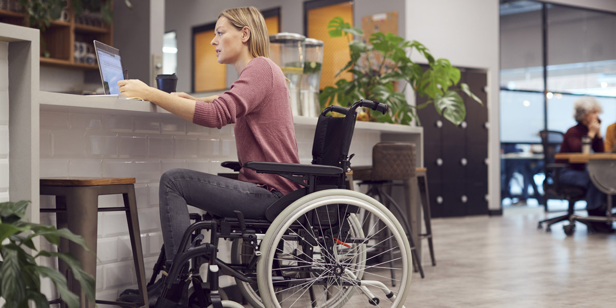 A data analyst in a wheelchair, using a laptop in a co-working space