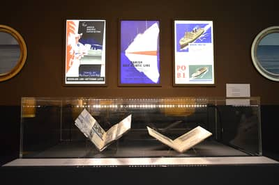 A photo of a showcase containing books, and three illustrations advertising cruise liners are above it. At both sides, there are graphics of ship porthole windows.