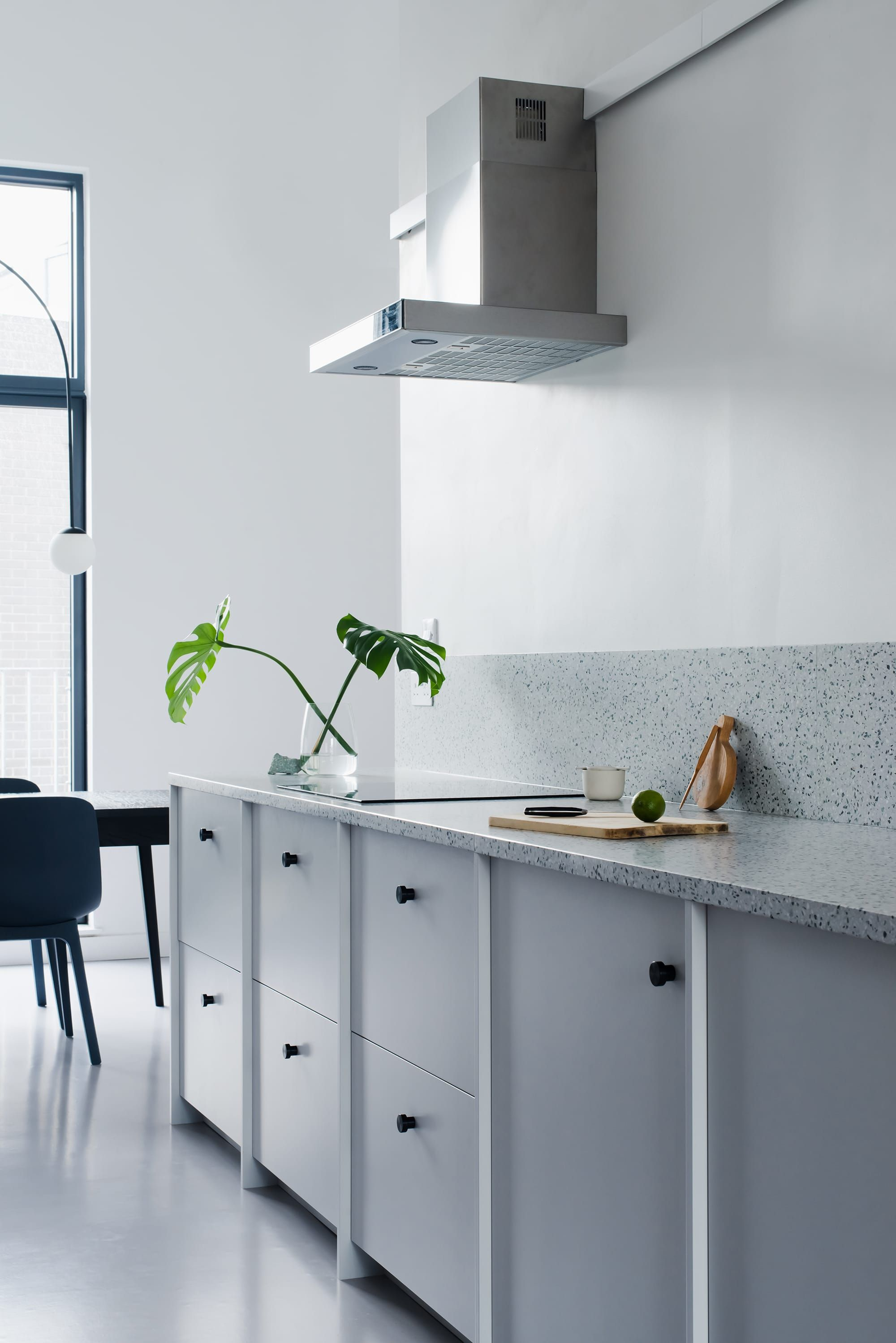 Low kitchen run with light grey cabinets and terrazzo worktop.