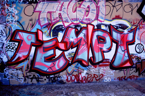 """A graffitied wall reaing """"Tempt""""in pinks, reds, and blues— the name of the graffiti artist who is the subject of the film."""