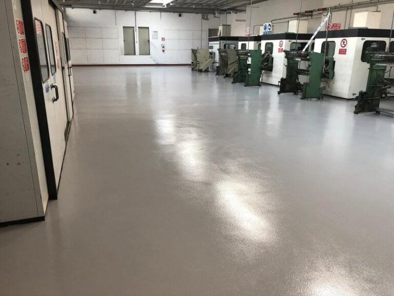 Macchinari industriali disposti su un pavimento in resina multistrato ad alta resistenza.