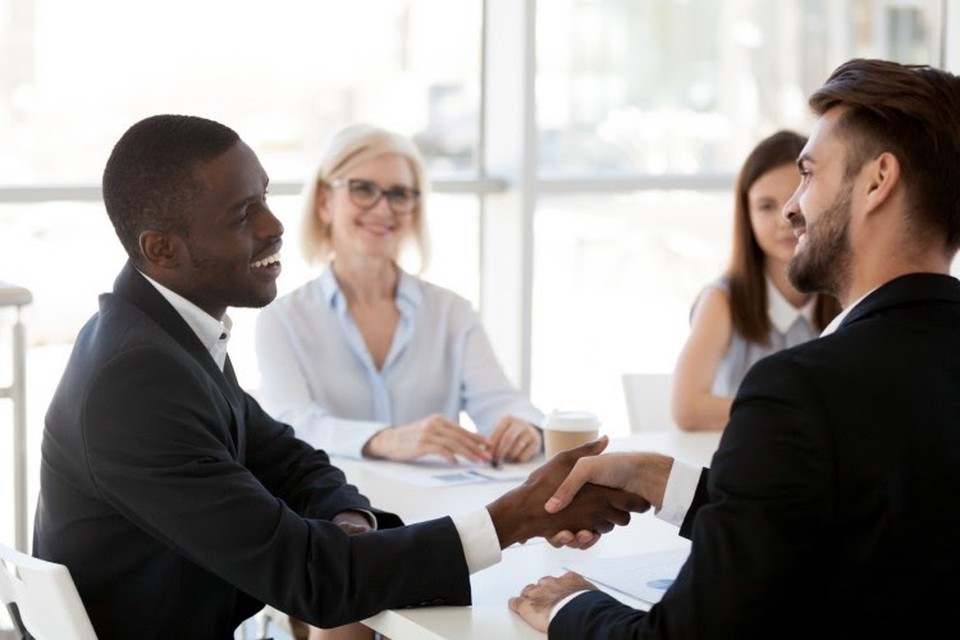 A candidate for a teaching job shakes hands with an interviewer during a group interview.