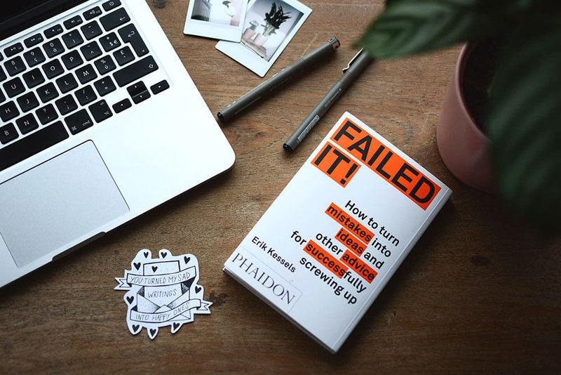 Um livro chamado Failed It! em cima de uma mesa. Também há um notebook, canetas, fotos, um adesivo e uma planta em cima desta mesa.