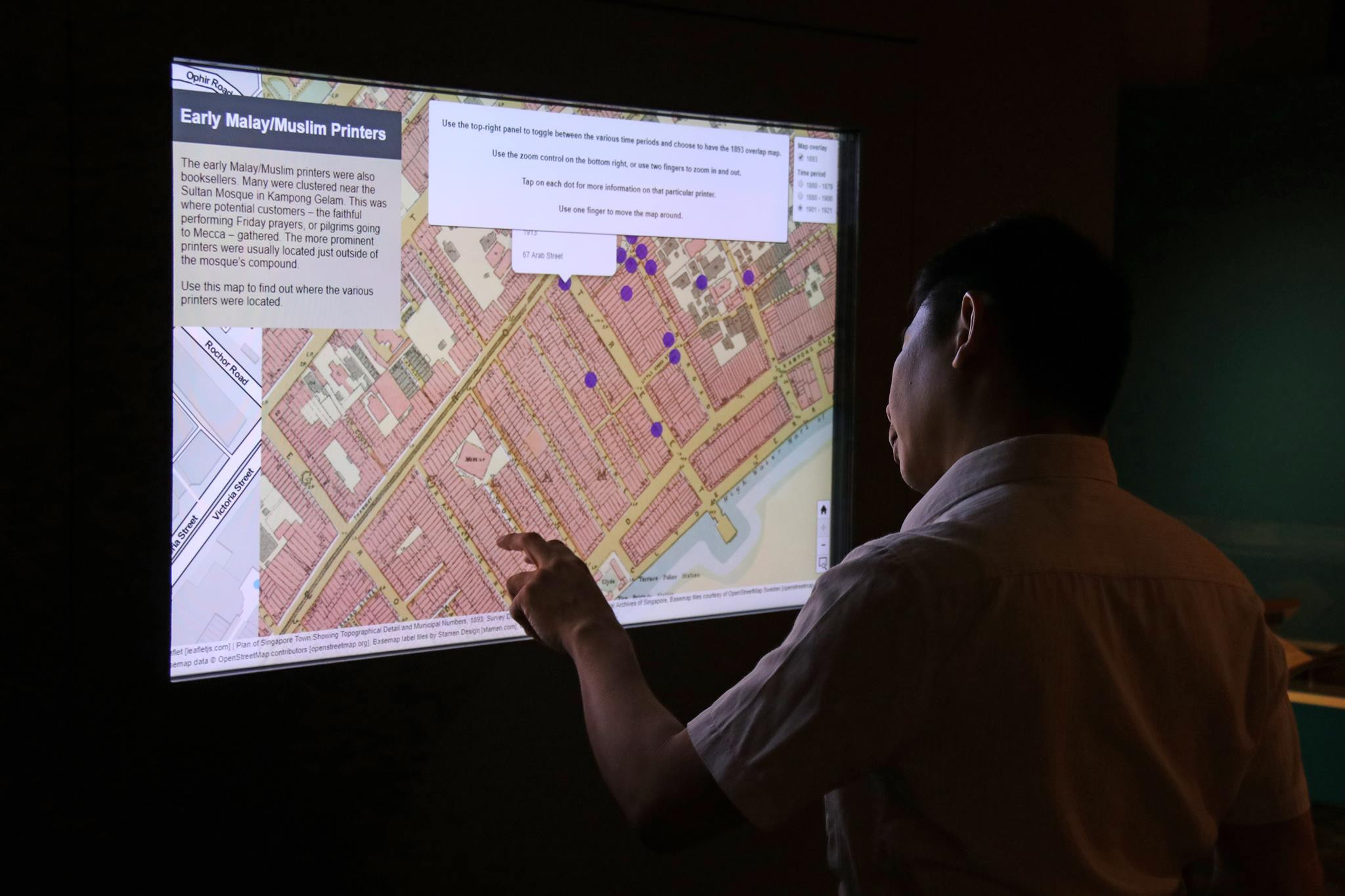 A man touches an interactive screen on the wall. The screen displays a city map with several map markers, along with the information box titled Early Malay Muslim Printers.