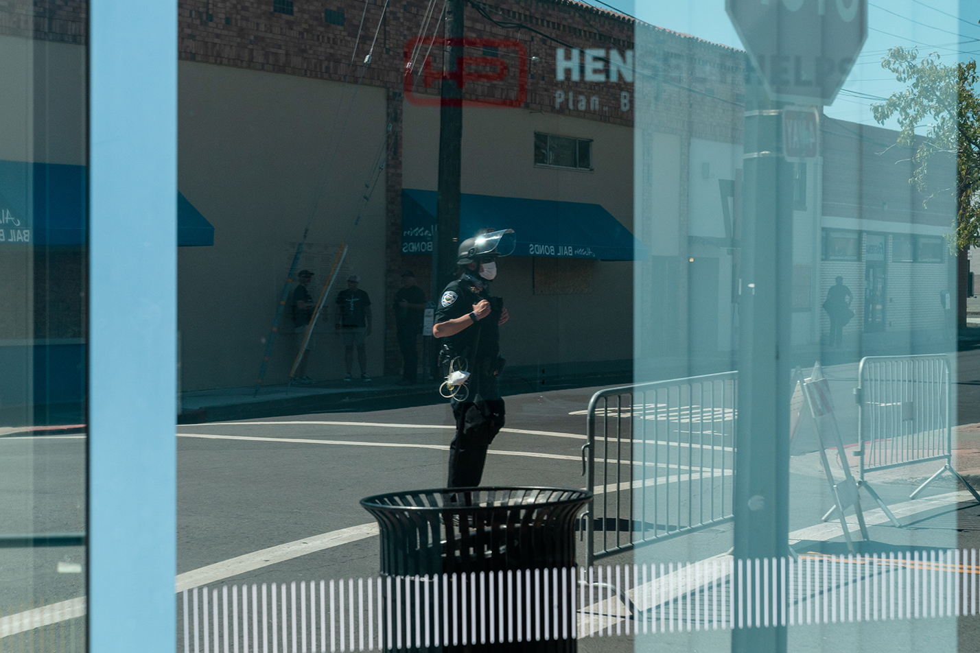 "A police officer is seen in the reflection of a window in downtown Martinez, California during the ""Zero Tolerance for White Supremacy"" protest on Sunday, July 12, 2020."